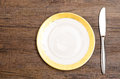 Porcelain dessert plate with knife on a wooden table Royalty Free Stock Photography