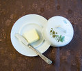 Porcelain plate with cover and silver knife with butter on a decorated cover - top view