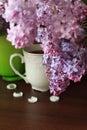 Porcelain teacup, lilac bouquet and white decors
