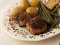 Pork burgers with potatoes and vgetables the Stock Image