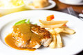 Pork chop with dilicious sauce and french fries Royalty Free Stock Photo