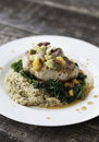 Pork chop sauteed over quinoa and greens with peach salsa Royalty Free Stock Photo