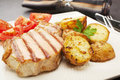 Pork chop steak or cooked on the griddle on a plate with garlic roast potatoes and tomato salad Royalty Free Stock Photo