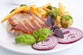 Pork chops with french fries and brussel sprouts and fresh basil Stock Photo