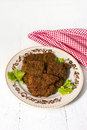 Pork chops and fresh lettuce leaves on a round dish Royalty Free Stock Images