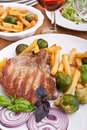 Pork chops with fries, brussels sprouts and wine Royalty Free Stock Image