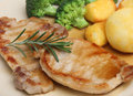 Pork loin meat steaks with vegetables roast potatoes broccoli and gravy Royalty Free Stock Photography