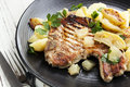 Pork meal grilled served with a potato apple and lemon salad Stock Photos