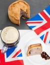 Pork pie and beer with flags closeup of a helping of english brown sauce a half pint of union jack on a black slate rustic Stock Images