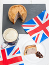 Pork pie and beer with flags helping of english brown sauce a half pint of union jack on a black slate rustic white table top Stock Photography