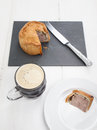 Pork pie and beer slice of english on a white plate a half pint of on rustic white table top with behind Royalty Free Stock Photography