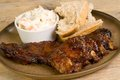 Pork ribs in barbecue sauce with coleslaw and crusty bread Royalty Free Stock Image