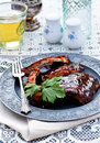 Pork ribs grilled bbq stacked on an antique plate against a light bright background smothered in a spicy smoky sauce the perfect Royalty Free Stock Photo