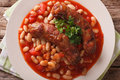 Pork sausages with beans and cooked tomatoes on a plate closeup. Royalty Free Stock Photo