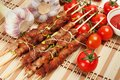 Pork skewers with cherry tomatoes and garlic herbs on a bamboo mat Stock Photos