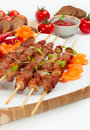Pork skewers with cherry tomatoes and garlic herbs on a bamboo mat Royalty Free Stock Images