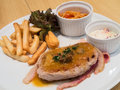 Pork steak with chips and bacon on white plate Stock Image