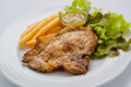 Pork steak with french fries and salad on a white background. Royalty Free Stock Photo