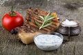 Pork steak with rosemary tomato and souse on old wooden table Royalty Free Stock Photo