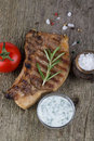 Pork steak with rosemary tomato and souse on old wooden table Stock Photography