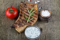 Pork steak with rosemary tomato and souse on old wooden table Stock Image