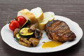 Pork steak with sauce mustard and grilled vegetables on the plate Royalty Free Stock Photos