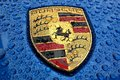 Porsche Logo Close Up on a bright blue car with rain drops Royalty Free Stock Photo