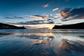 Port erin beach at sunset in the isle of man with the harbour and bradda head silhoutetted and clouds reflected on the wet sand Royalty Free Stock Images