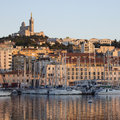 Port of marseille french riviera the harbor in the late afternoon sunlight looking towards the cathedral de notre dame de la garde Stock Image
