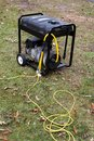 Portable generator electric with power cords attached sits on grass Royalty Free Stock Image