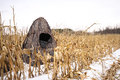 Portable hunting blind a camouflaged sits in a corn field during winter Royalty Free Stock Image