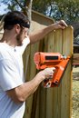 Portable nail gun man wearing safety glasses uses a to attach wood pickets to the rail as he builds a privacy fence in the Royalty Free Stock Photo