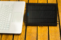 Portable solar charger sitting on wooden surface next to laptop computer, as seen from above, modern technology concept Royalty Free Stock Photo
