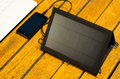 Portable solar charger sitting on wooden surface next to laptop computer and mobile phone, as seen from above, modern Royalty Free Stock Photo