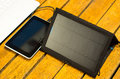 Portable solar charger sitting on wooden surface next to laptop computer and tablet, as seen from above, modern Royalty Free Stock Photo