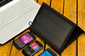 Portable solar charger sitting on wooden surface next to laptop computer and three smartphones, as seen from above Royalty Free Stock Photo