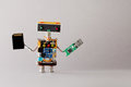 Portable storage devices usb memory card concept. Abstract robot toy with tech accessories. gray background.