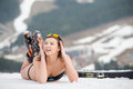 Portait of sexy woman skier is relaxing on the snowy slope in the mountains. Wearing swimsuit, boots and sunglasses Royalty Free Stock Photo