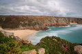 Porthcurno is located in the far west of cornwall the gorgeous fine soft sand washed by a turquoise sea is surrounded by high Royalty Free Stock Images