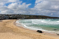 Porthmeor beach st ives cornwall england with white waves breaking towards the shore and blue sky and clouds known for surfing and Stock Images