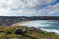 Porthmeor st ives cornwall england with white waves beach breaking towards the shore and blue sky and clouds known for surfing and Royalty Free Stock Photo