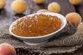 Portion of apricot jam on rustic wooden background Stock Images