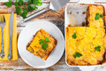 Portion of delicious moussaka on plate and in gratin dish Royalty Free Stock Photo