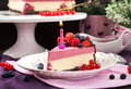 Portion of delicious raspberry cheesecake decorated with fresh berries chocolate and candle Royalty Free Stock Images