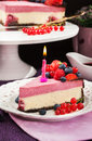 Portion of delicious raspberry cheesecake decorated with fresh berries chocolate and candle Stock Image