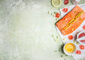 Portion of fresh salmon fillet with lemon slices oil and ingredients for cooking on light wooden background top view place for Royalty Free Stock Photography