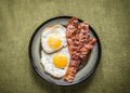 Portion of fried eggs with bacon close up Royalty Free Stock Images
