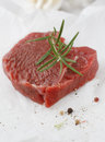 Portion healthy lean steak topped fresh rosemary as seasoning waiting to be cooked nutritious meal Royalty Free Stock Photos