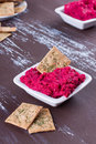 Portion of hummus beetroot with crackers Royalty Free Stock Image
