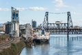 Portland, USA - March 3, 2016: Industrial view in Oregon with ship, cranes, factory and railroad by Willamette River Royalty Free Stock Photo